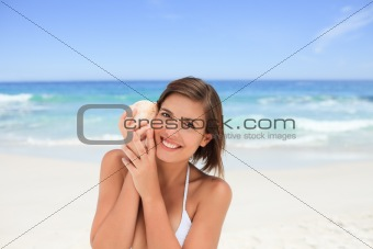 Beautiful woman listening to her shell