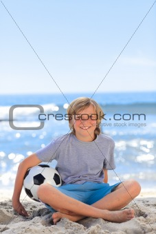 Boy  with his ball on the beach