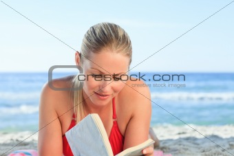 Adorable woman reading a book on the beach