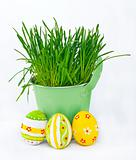 Colorful Easter eggs next to the bucket with the spring grass