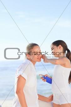 Little girl applying sun cream on her mother's face