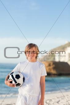 Little boy with a ball on the beach