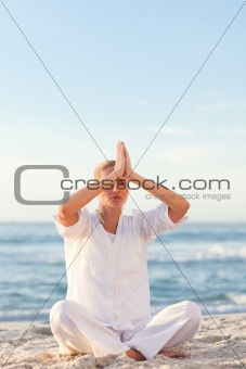 Active woman practicing yoga on the beach