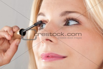 pretty woman applying her make-up mascara