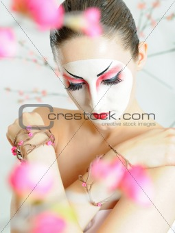 japan geisha woman with creative make-up in sakura garden