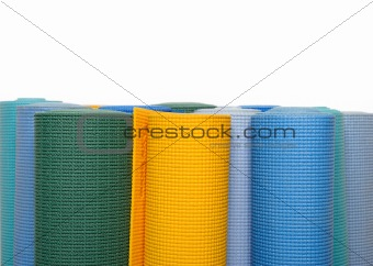 many colorfull yoga mats as a background. isolated on white