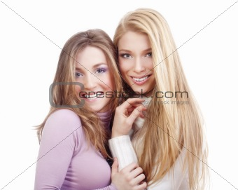portrait of two sisters with long hair standing smiling - isolated on white