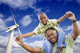 Happy African American Father and Son with Wind Turbine Over Blue Sky.