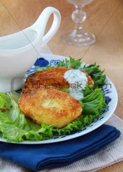 potato patties with green salad and yoghurt sauce