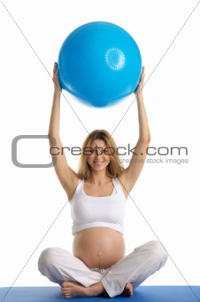Pregnant woman practicing yoga with ball
