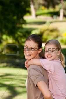 Beautiful mother giving daughter a piggyback