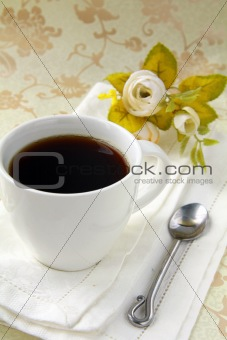 cup of black coffee and flowers on a vintage background