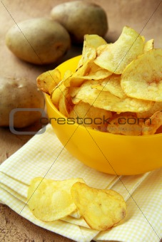 potato chips in a yellow cup, and fresh potato