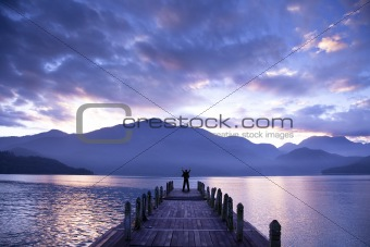 Man stand on a pier and watching the mountains and lake