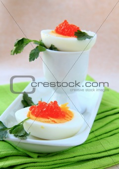 appetizer egg with red caviar on a white plate