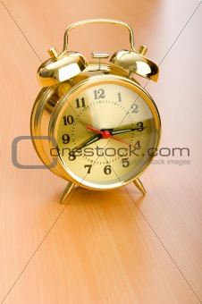 Alarm clock on the wooden table