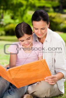 Mother and her daughter looking at their album photo
