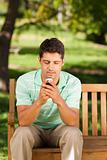 Man with his phone on the bench