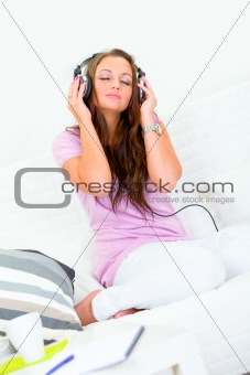 Pretty woman relaxing on couch and listening music in headphones