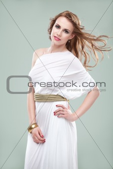 portrait of young woman in greek inspired white dress, smiling,