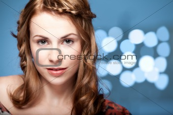 a beauty, head and shoulders portrait of a young, blonde woman, looking fresh and smiling. she wears natural make-up and hair style and the background is blue, with faided white lights.