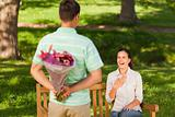 Young man offering flowers to his wife