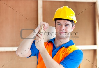 Assertive young male worker with a yellow helmet carrying a wood