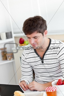 Bright man having breakfast and using his laptop in the kitchen