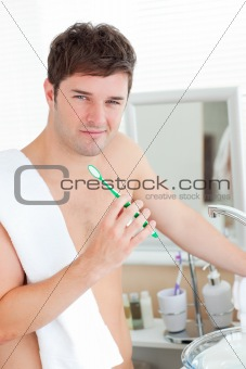 Positive young man with a towel brushing his teeth in the bathro