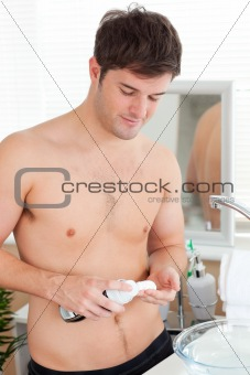Positive caucasian man ready to shave in the bathroom