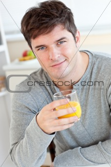 Attractive young man drinking orange juice in the kitchen