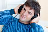 cheerful man listening music with headphones on lying in the liv