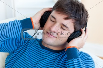 peaceful man listening music holding his earphones lying on the
