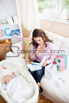 Bright woman sitting on the sofa with bags reading a card while