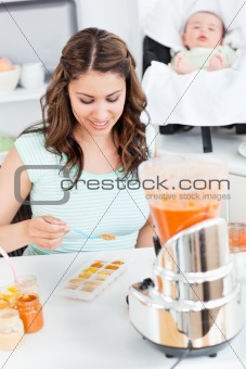 Caring mother preparing food for her lovely baby in the kitchen