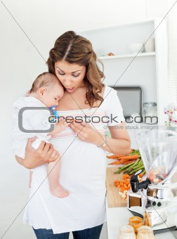 Caring mother preparing food for her adorable baby in the kitchen