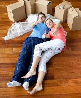 happy couple lying on the floor in their new house doing thumbs-