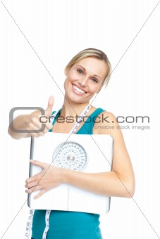 Attractive young woman holding a weight scale