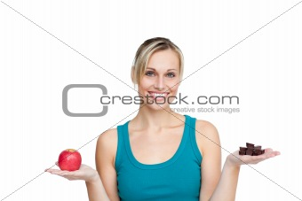 Beautifull woman comparing apple with chocolates