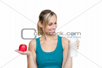 Smiling beautiful woman holding water and apple