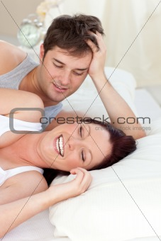 Glowing caucasian couple lying on bed