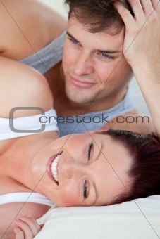Portrait of a young pregnant woman and of her husband lying on t