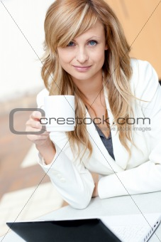 Bright businesswoman holding a cup of coffee in front of her lap