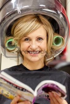 Delighted woman reading a magazine with hair curlers