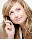 Thoughtful businesswoman talking on phone in her office