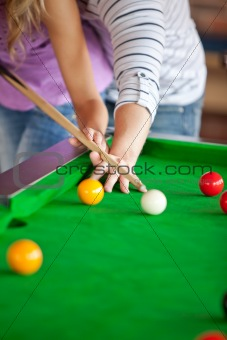 Attentive boyfriend teaching his girlfriend how to play pool