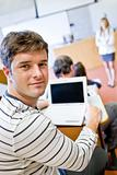 Close-up of a bright male student using a laptop during a university lesson