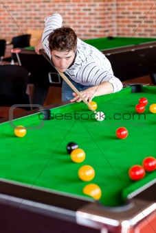 Concentrated young man playing snooker