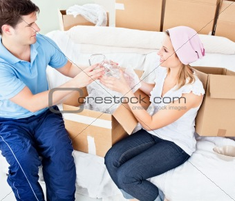 Affectionate young couple unpacking boxes with glasses