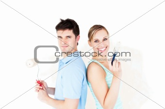 Charismatic couple painting a room